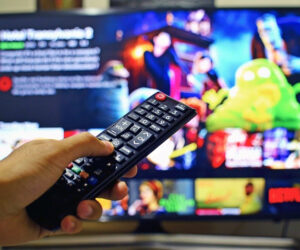 OTT CTV image of someone controlling smart TV remote