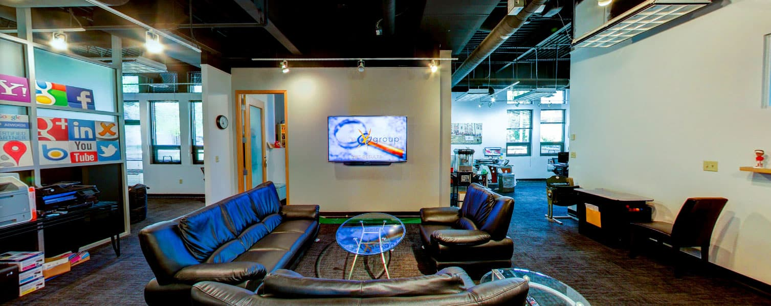 inside of the Xcite office showing tv, couches and open concept