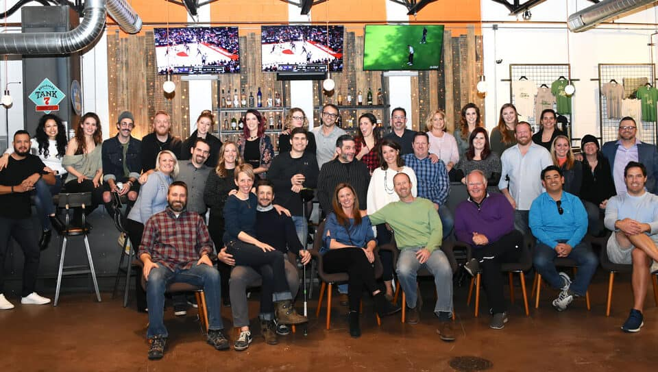 xcite employee family picture with everyone in front of the bar